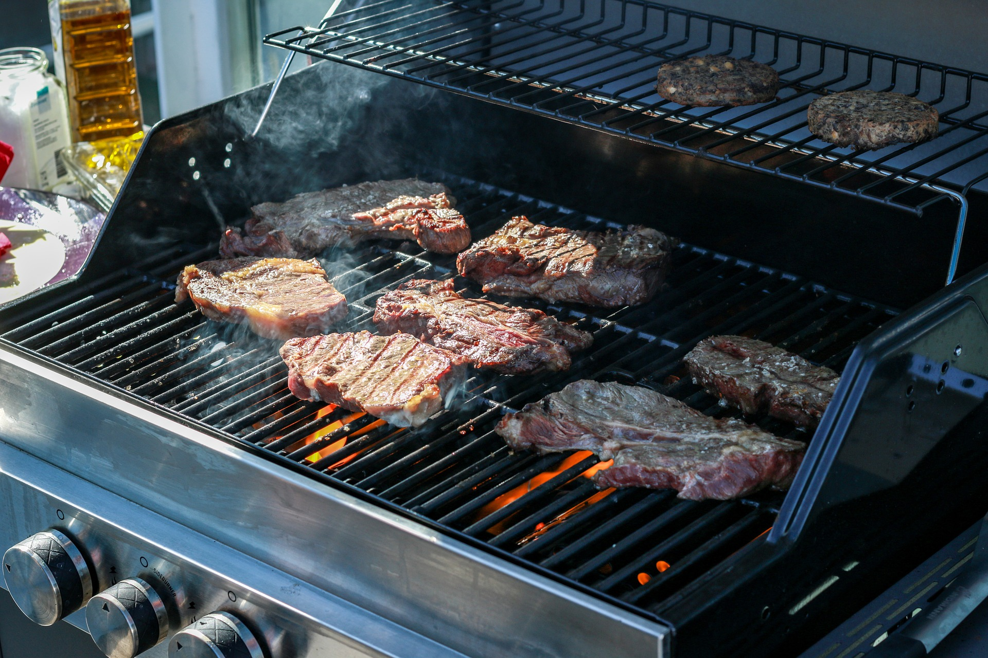 lots of meat on a gas grill