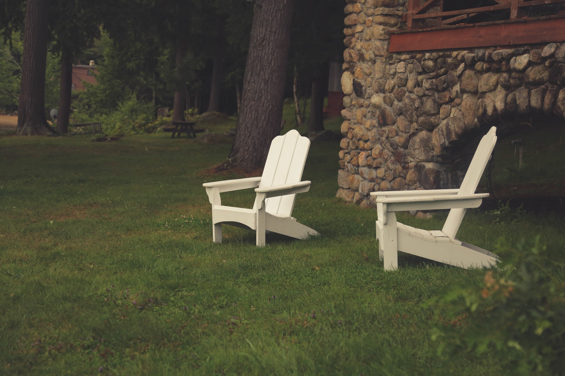 white resin adirondack chairs in a yard, resin patio furniture