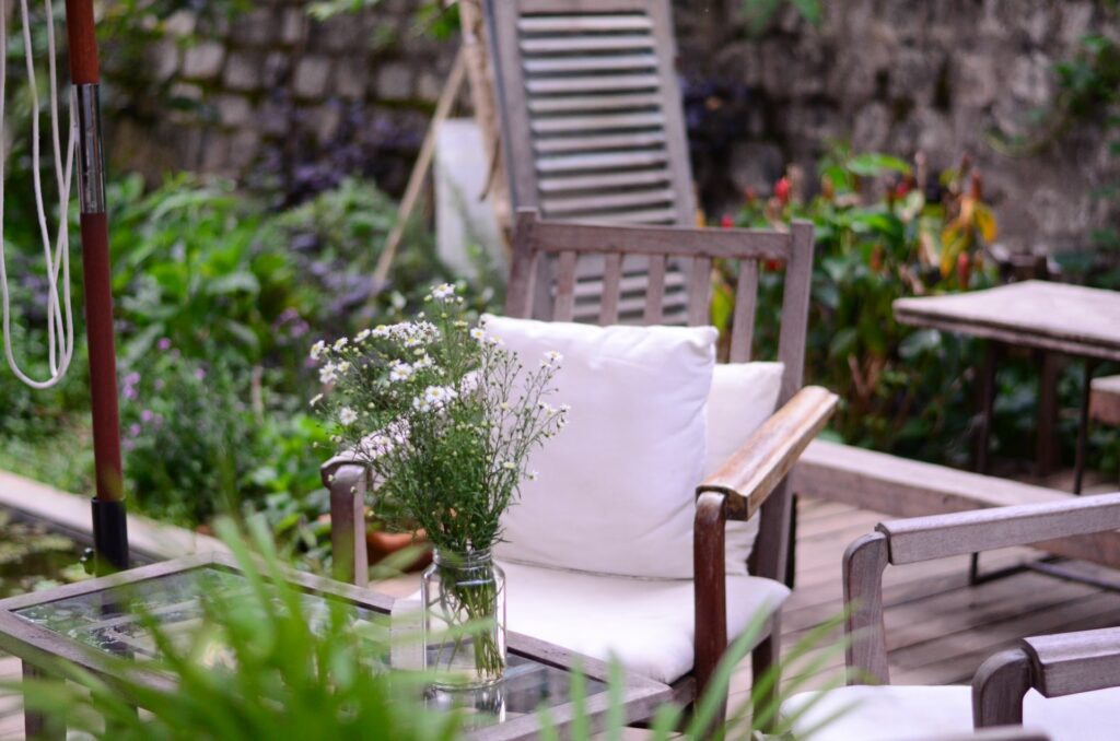 wooden outdoor furniture with flowers in the foreground
